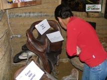 Visitante lendo informações sobre o Silhão, peça de montaria feminina, exposto no Rancho do Tropeiro em 2010.